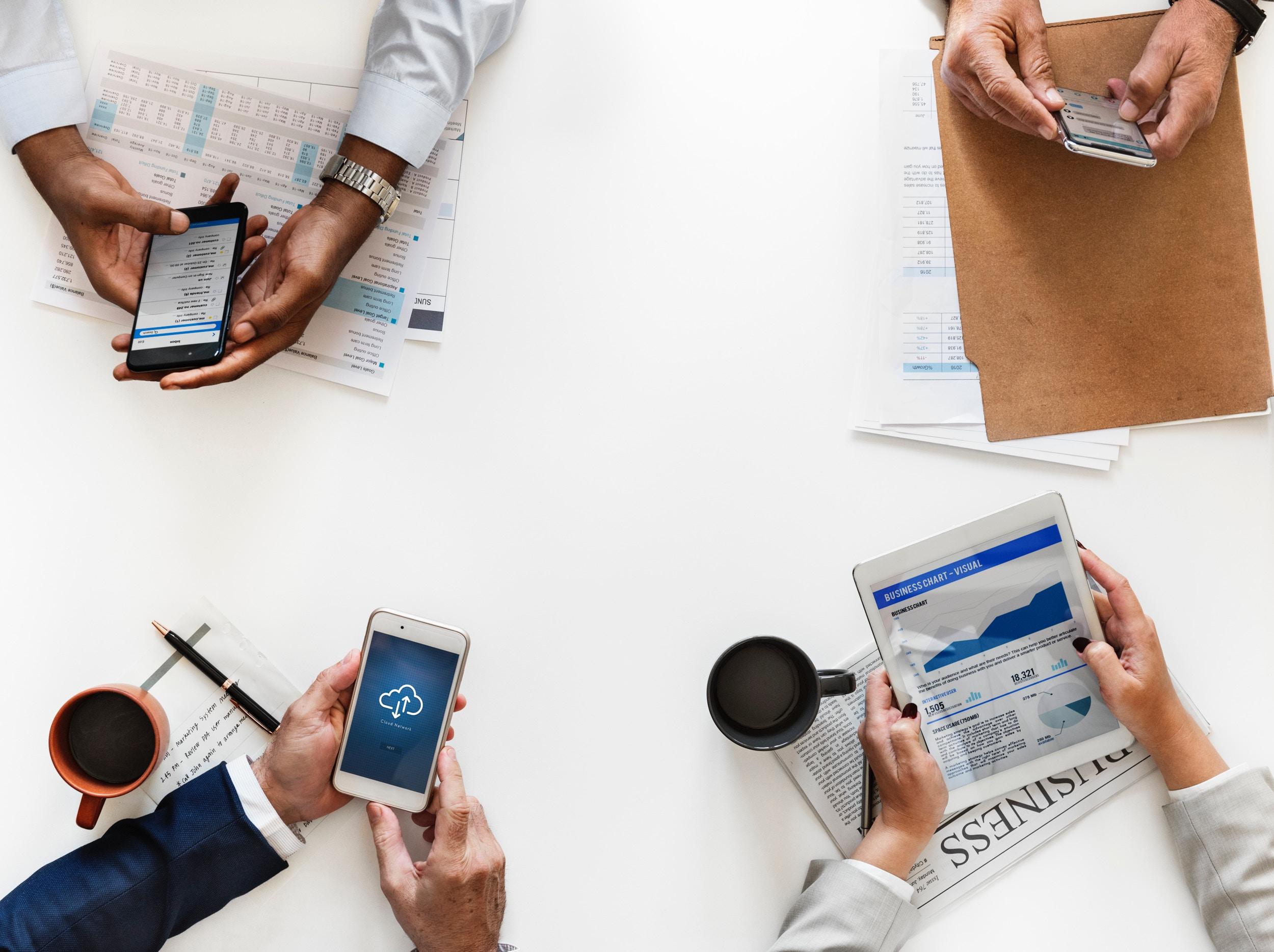 4 salariés qui utilisent des smartphones et des tablettes sur un bureau blanc