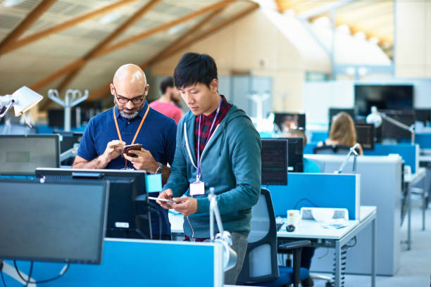 Deux employés qui regardent leur portable dans des bureaux