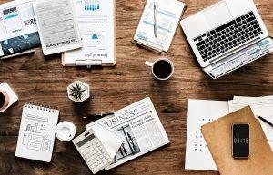 Table en bois avec tasse de café, ordinateur et papiers d'entreprise