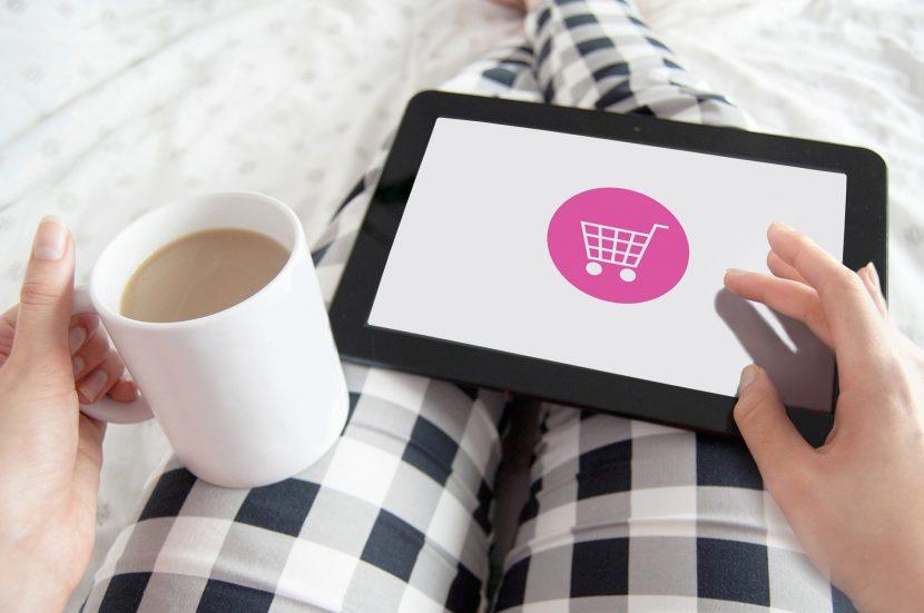 Femme qui passe une commande en ligne depuis sa tablette et qui tient une tasse dans l'autre main