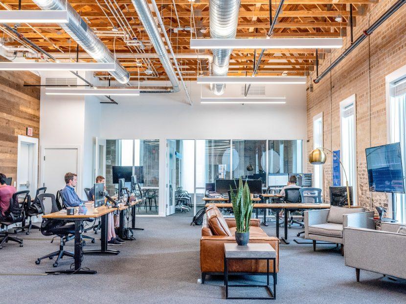Grande pièce au style industriel dans laquelle sont installés de nombreux bureaux et des canapés
