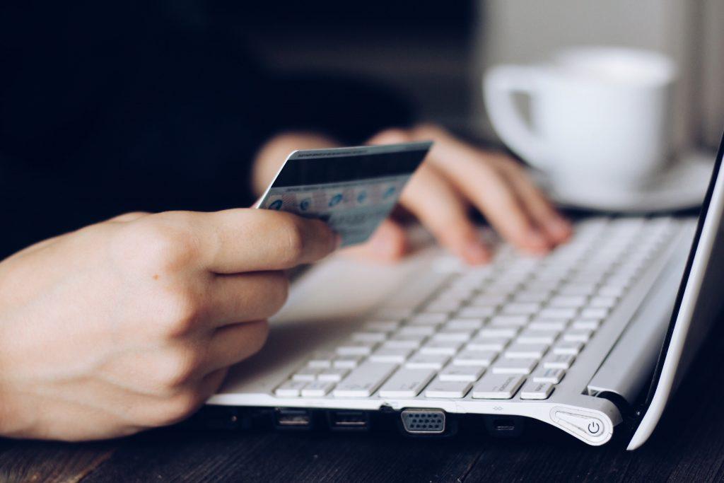 zoom sur les mains d'une personne tenant une carte bancaire près d'un clavier d'ordinateur