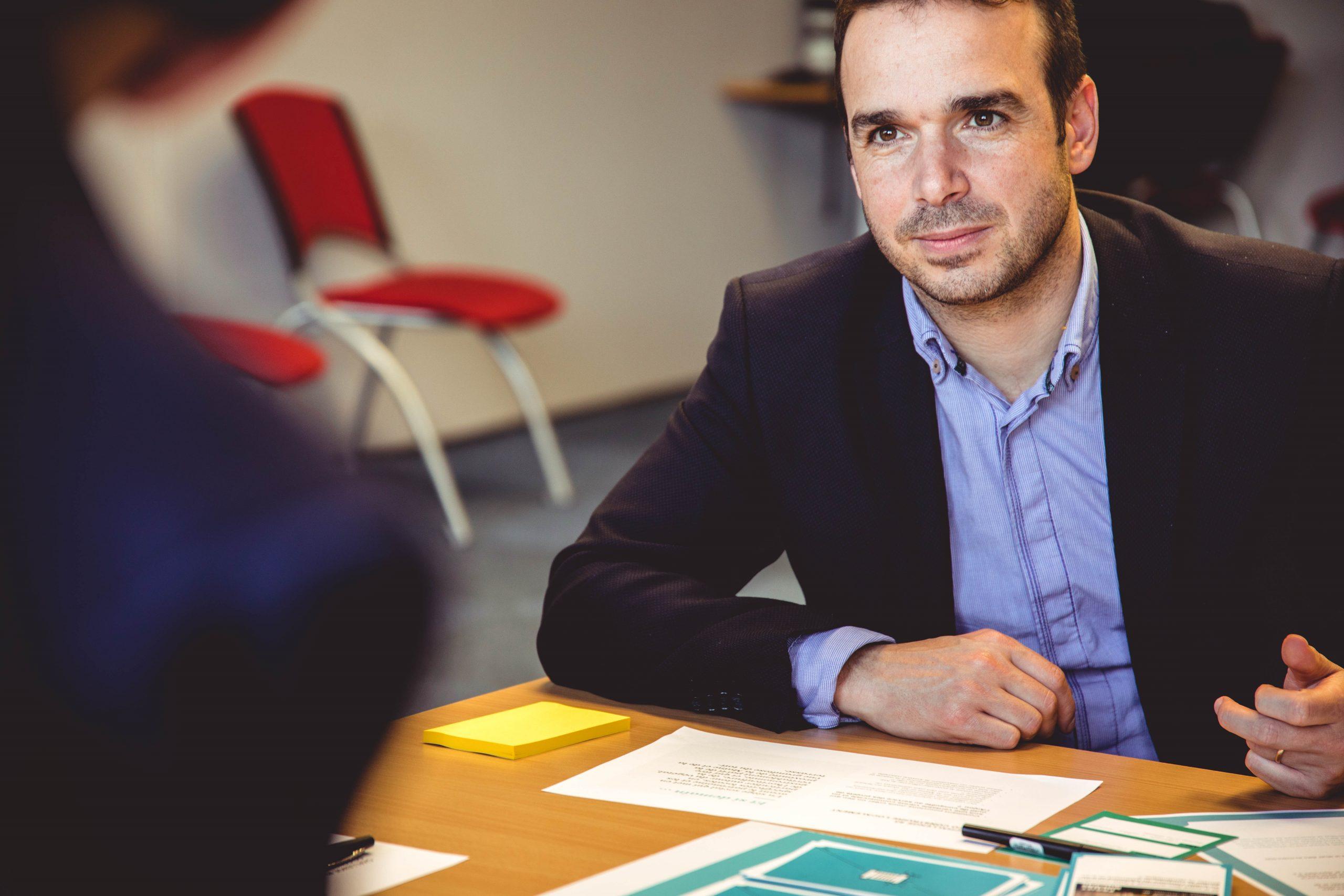 homme portant une chemise bleue et une veste foncée assis derrière un bureau